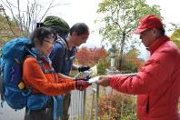 登山届の提出など安全登山を呼びかける県警山岳救助隊員(右)=秩父市三峰の三峰ビジターセンターで