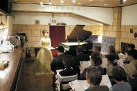 演奏前に曲の解説をする安達萌さん=神戸市中央区のアマデウスで、田中博子撮影