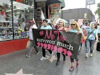 「私も」と書いた横断幕を掲げ、ハリウッド中心部を行進するセクハラ被害者ら=米西部カリフォルニア州ハリウッドで2017年11月12日、長野宏美撮影