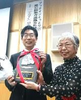 授賞式で笑顔を見せる橋本道範さん(左)とサンライズ出版の岩根治美・専務取締役