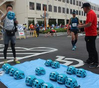 夏の富士山を駆け上がる今年の「富士登山競走」では、試験的にヘルメットの貸し出しが行われた=山梨県富士吉田市役所前で7月28日、小田切敏雄撮影