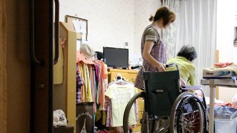 高齢の入所者の就寝を手伝う女性介護士