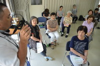 Elderly women listen to the voice of a fraudster during an anti-crime class in Osaka's Chuo Ward on July 13. (Mainichi)