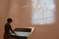 「隅田川両岸景色図巻」のタッチパネルに触れると当時の地図がスクリーンに映し出される=東京都墨田区亀沢2のすみだ北斎美術館で