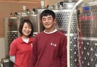 初の自社製ワインを醸造しているタンクの前で、笑顔を見せる「兎ッ兎」の前岡美華子社長(左)と寺谷英樹農場長