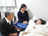仮設住宅で暮らす橋村ももかさん(右)を訪ねる東俊裕さん(左)。車いすが室内に入らないため、橋村さんは寝た状態で過ごすことが多い。中央は母りかさん=熊本県益城町のテクノ仮設団地で2017年10月31日、野倉恵撮影