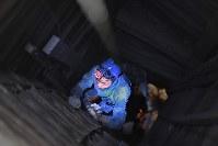 深さ11.5メートルの穴の中での金鉱石の採掘を終え、はしごをつたって穴から出るボン・エムさん=カンボジア・バタンバン州プノンプロックで2017年8月25日、川平愛撮影