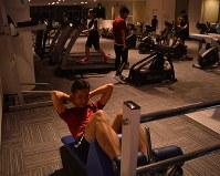 本社ビル11階にあるフィットネスクラブで「健康改善チーム戦」に備えてトレーニングする社内チーム「リサリサ」のメンバー=東京都大田区で