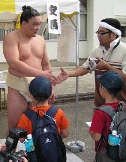 握手会でファンと握手する安馬(左)=群馬県富岡市の富岡巡業会場で、8月3日午前8時半ごろ、飯山太郎撮影