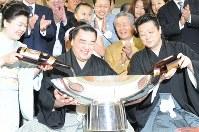 初優勝し、賜杯に酒を注がれ笑顔の日馬富士(中央)=東京都江東区の伊勢ケ浜部屋で2009年5月24日午後7時12分、馬場理沙撮影