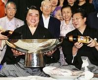 全勝優勝し、関係者らが見守る中、伊勢ケ浜親方(右)に酒をついでもらう日馬富士=東京都江東区で2012年9月23日午後7時10分、小出洋平撮影