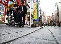 繁華街で車椅子に乗りながら歩道の段差などを調べる参加者たち=東京都千代田区で2017年11月1日、小出洋平撮影