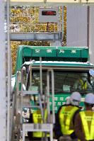 空間放射線量を測定するゲートをくぐり、最終処分場に入る放射性廃棄物を積んだトラック=福島県富岡町で2017年11月17日午前10時53分、喜屋武真之介撮影