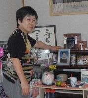夫芳明さんの遺影に語りかける高山ひろみさん。すぐ上に骨つぼが=北九州市小倉南区の自宅で10月12日