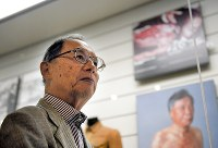 Takeshi Yamakawa looks at the displays at Nagasaki Atomic Bomb Museum in Nagasaki on Nov. 9, 2017. Behind him is a photo of Sumiteru Taniguchi, with burns all over his back. (Mainichi)