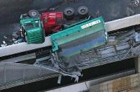 横転し側壁に乗り上げた大型ダンプカー=東京都港区で2017年11月21日午前8時41分、本社ヘリから宮武祐希撮影