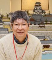 福山城の巨大模型を作成している和久井裕道さん。背景は福山城の巨大模型の天守閣=福山市西町1のエフピコRiMで、真下信幸撮影