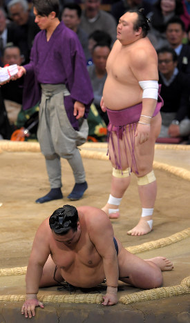 Kisenosato, foreground, leans with his hands on the clay mound after being defeated by Takarafuji, standing on the mound at right, at Fukuoka Kokusai Center, on Nov. 20, 2017. (Mainichi)