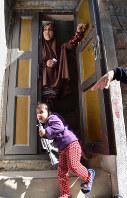 ヨルダン川西岸で暮らすハナンさんと娘のサラちゃん。おもちゃの銃を持った子供が目立つ=2017年10月18日