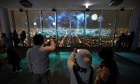 Visitors take photographs of a projection mapping display on the observation deck of the