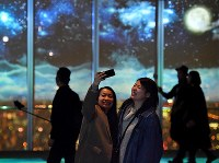 Visitors take photographs on the observation deck of the
