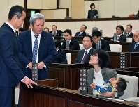 Kumamoto Municipal Assembly member Yuka Ogata, right, is seen with her son at her seat in the assembly chamber on Nov. 22, 2017. Speaker Yoshitomo Sawada is seen to the left. (Mainichi)
