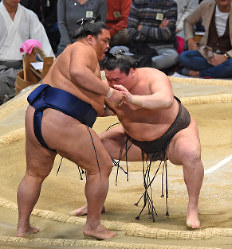 Yokozuna Hakuho, right, forces out sekiwake Mitakeumi to remain in the lead on Nov. 23, Day 12 of the Kyushu Grand Sumo Tournament, at Fukuoka Kokusai Center in Fukuoka. (Mainichi)