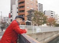 かつての深川蛤町あたりにたたずむ春風亭一之輔さん。奥に見えるのが再現された門前仲町の火の見櫓。半鐘がつるされているのが見える=東京都江東区で