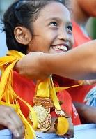 チームが優勝し、表彰式で金メダルをかけてもらい笑顔の女の子=フィリピン・ネグロスオクシデンタル州タリサイで2017年8月5日、川平愛撮影