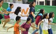 リオ五輪ラグビー7人制女子日本代表の小出深冬さん(中央)と手をつないで走る子どもたち=フィリピン・ネグロスオクシデンタル州タリサイで2017年8月4日、川平愛撮影