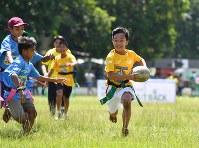 裸足でピッチを走る子どもたち。以前は、ほとんどの子どもたちがラグビーを知らなかった。この日、子どもたちは初めての大会に臨んだ=フィリピン・ネグロスオクシデンタル州タリサイで2017年8月5日、川平愛撮影