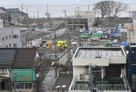 更地が広がる駅周辺。中央右は1日だけ行われたイベント「いといがわ復興マルシェ」。火元となった店舗は左端中央の灰色の建物の手前にあった。奥は日本海=新潟県糸魚川市で2017年11月18日、藤井達也撮影