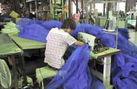 産業用ネットの縫製作業を続ける実習生のベトナム人男性=岡山県備前市の橋本産業で2017年9月、近藤大介撮影