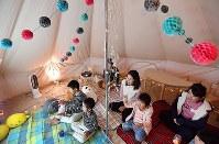 屋外に張ったテントでアニメを見る子どもたち=大阪市鶴見区で2017年11月4日、猪飼健史撮影