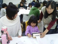 宮本さん(右)に教わりながらオルゴールを演奏して楽しむ親子=毎日ホールで