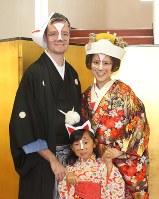きつねのメークをして花婿・花嫁役として参加したマケイ・アダムさんとマケイ・知美さん夫妻と、付き添いをした子供=さくら市の喜連川公民館で