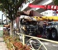 衝突・炎上して道路をふさいだトレーラーの撤去作業=東京都北区で