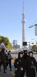 東京スカイツリーを背に浅草寺方面に向かって歩く忍者百人衆=東京都台東区で2017年11月25日、大西康裕撮影