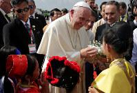 空港で、地元の子供たちから歓迎を受けるフランシスコ・ローマ法王=ヤンゴンで2017年11月27日、ロイター