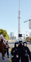 東京スカイツリーを背に浅草寺方面に向かって歩く忍者百人衆=東京都台東区で、大西康裕撮影