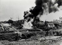 火炎放射器で丘の斜面をぬぐうようにして進む米軍。沖縄戦で多用され、洞くつや岩陰にこもる守備軍を苦しめた