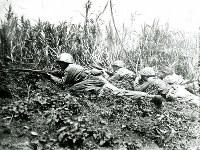 銃を構えた兵士と共にほふく前進する米軍の映画カメラマン。沖縄戦は多くのフィルムを残し、戦いの実相を伝える