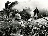 投降者に銃を向ける海兵隊員と、その発砲を制止する隊員。発煙弾を洞穴に投げ込み、出てこさせた