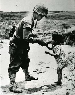 米兵から与えられた水を一心に飲む女児。洞穴で発見・保護された。水筒を離すまいとする細い腕が長い渇きを語る
