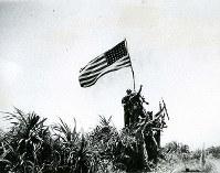 星条旗を掲げ、勝利のポーズをとる米兵たち。6月21日の撮影と記録されている。日本兵の散発的抵抗は続いていた