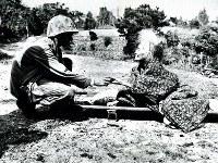 海兵隊員が差し出すキャンデーを受ける女性