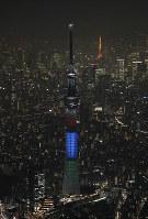 東京パラリンピックの1000日前イベントで、三色に彩られた東京スカイツリー。右奥は東京タワー=東京都墨田区で2017年11月29日午後6時9分、本社ヘリから撮影