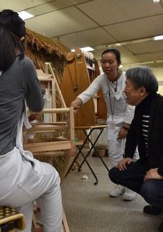 製品を作る過程を池上さん(右)に説明するタン・ナリさん(中央)=豊橋市で