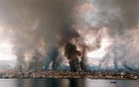 阪神大震災で火災による黒煙が上がる神戸市。震災で24万棟以上の家屋が全半壊し、約7000棟が全焼した=1995年1月17日、本社ヘリから橋口正撮影