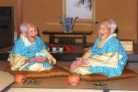 長寿の双子姉妹、成田きんさん(左)と蟹江ぎんさん。100歳を過ぎても明るく元気な姿は国民的な人気を集めた=名古屋市緑区で1999年11月6日、鮫島弘樹撮影